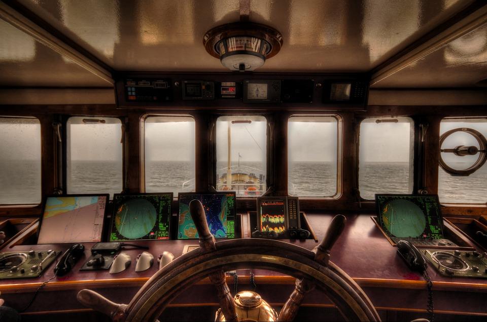 Vue sur la mer depuis la cabine d'un bateau. Au premier plan, la barre de navigation et des cartes avec des radars.