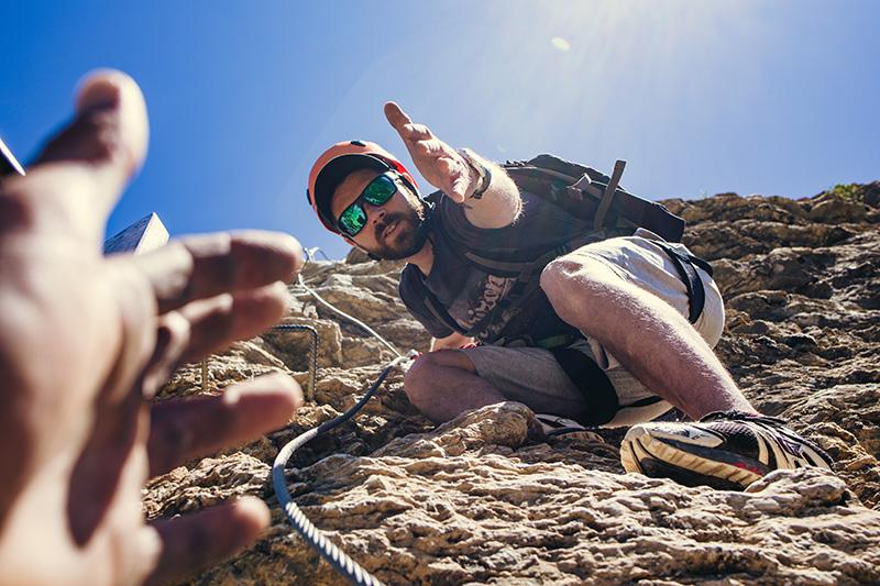 Homme accroché à une falaise qui tend sa main vers une autre main.