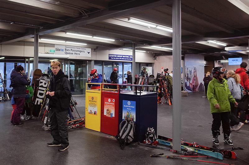 Entrée de la station de ski Coronet, Queenstown, Nouvelle Zélande. De grand panneaux indique les files d'attentes pour les bus. Les poubelles sont colorées et ont des images et information sur quoi jeter où.