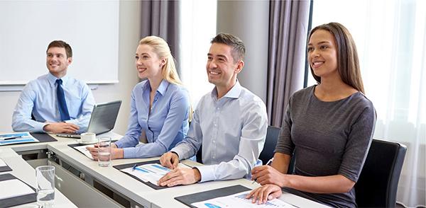 Groupe de 4 gens d'affaires écoutant avec un sourire