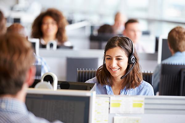 Jeune femme avec un casque téléphonique, devant un ordinateur. Elle est entourée de collègues dans un CCC.