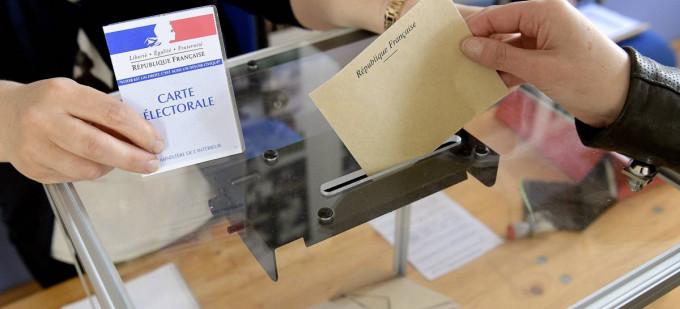 Élection en France: une main glisse une enveloppe dans un urne transparente. Une autre main tient une carte électorale