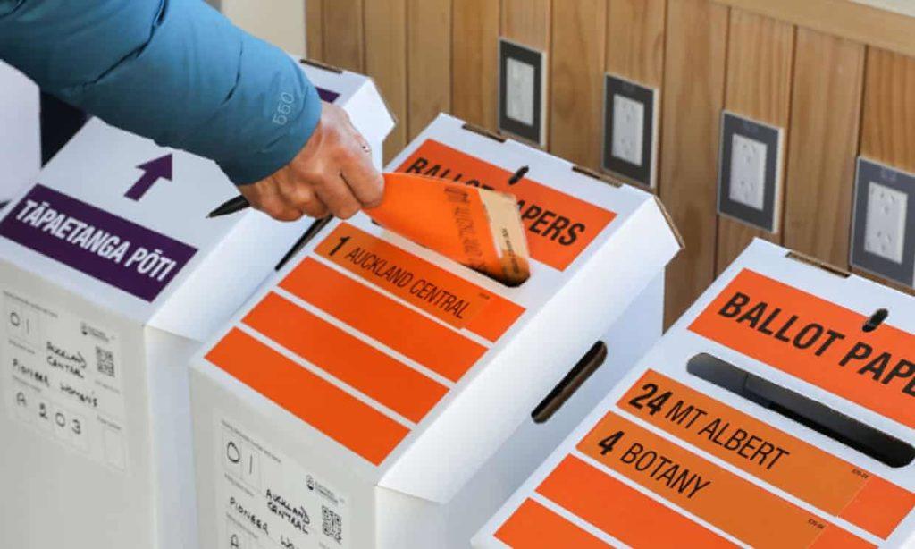 Élection en Nouvelle Zélande: une main dépose un bulletin dans une urne en carton.