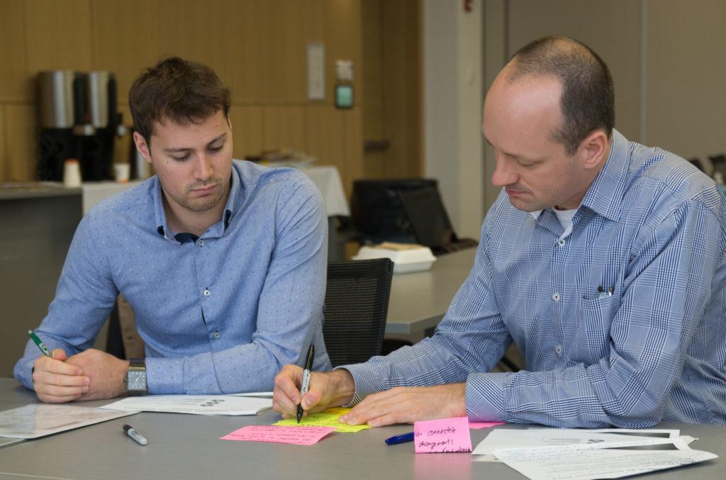 Deux hommes écrivent sur des post-its.