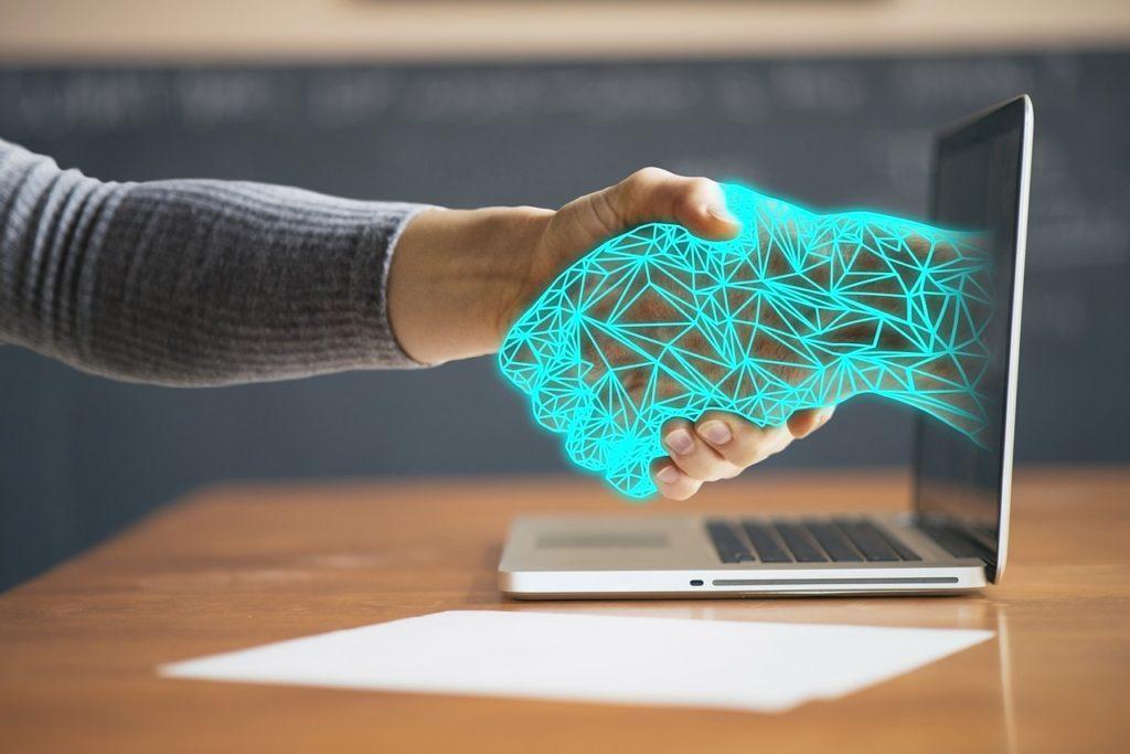 Main d'un homme qui sert la main d'un robot qui sort de l'écran d'ordinateur.